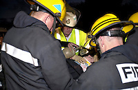 Paramedic ambulance crew and firefighters attending a road traffic accident involving a car stolen by a joyrder that was then involved in a head on crash. The paramedic is bracing the casualty's neck whilst the firefighter is using a bag and mask to assit her with her breathing. She has been extricated from the vehicle and has been placed on a spinal board.