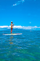 Young woman standup paddle boarding, Maui