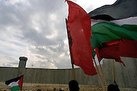 Palestinian demonstrators hold national flags towards Israeli soldiers during a demonstration against the wall in Qalqilia, November 9th was marked as a global day against the separating fence. Photo by Quique Kierszenbaum