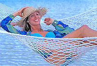 Woman with beach hat smiles as she relaxes in a hammock at the beach.