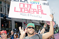"A man wears a red USA hat and carries a sign reading ""Black, Gay, and Not a Liberal / #walkaway"" in the Straight Pride Parade in Boston, Massachusetts, on Sat., August 31, 2019. The parade was organized in reaction to LGBTQ Pride month activities by an organization called Super Happy Fun America."