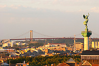 A view over the rooftops and city of Bordeaux with the Pont d'Aquitaine over the Garonne river at sunset.  The statue 'La Liberte brisant ses fers' (Liberty breaking her chains)