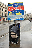 A man shelters from the rain in the Strand while holding a placard advertising a beauty parlour.