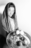 Portrait of a young woman wearing a veil and offering a plate of fruit.