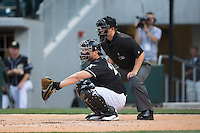 Charlotte Knights catcher George Kottaras (20) sets a target as home plate umpire Sean Barber looks on during the game against the Louisville Bats at BB&T BallPark on May 12, 2015 in Charlotte, North Carolina.  The Knights defeated the Bats 4-0.  (Brian Westerholt/Four Seam Images)