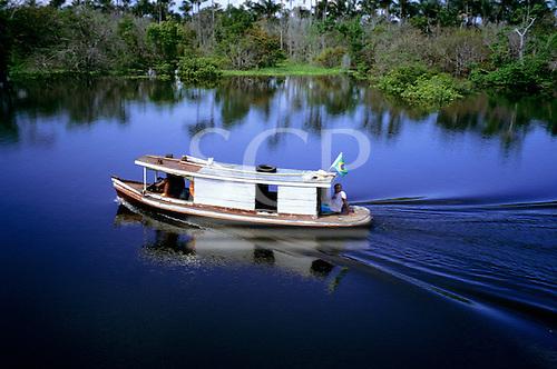 Manaus, Amazonas State, Brazil. Small riverboat bearing the Brazilian flag on the Amazon River.