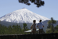 Tourists viewing information board at foot of northern side of Mount Teide volcano Tenerife canary islands spain