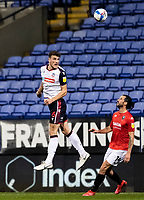 Bolton Wanderers' Ryan Delaney (left) heads under pressure from Salford City's George Boyd<br /> <br /> Photographer Andrew Kearns/CameraSport<br /> <br /> The EFL Sky Bet League Two - Bolton Wanderers v Salford City - Friday 13th November 2020 - University of Bolton Stadium - Bolton<br /> <br /> World Copyright © 2020 CameraSport. All rights reserved. 43 Linden Ave. Countesthorpe. Leicester. England. LE8 5PG - Tel: +44 (0) 116 277 4147 - admin@camerasport.com - www.camerasport.com