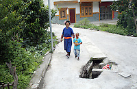 A Tibetan woman and child walk past a hole in a road in a town in the south-east Tibetan Plateau, in Sichuan Province, western China.