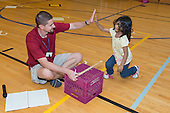 MR / Schenectady, NY. Zoller Elementary School (urban public school). Kindergarten inclusion classroom. Gym teacher does high five with student, commending her for her efforts during physical education assessment to test flexibility. MR: Mel16, Ram13. ID: AM-gKw. © Ellen B. Senisi.