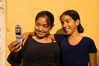 Local teenagers taking camera phone picture photo in front of yellow walls in todays communication in village of Antigua Guatemal