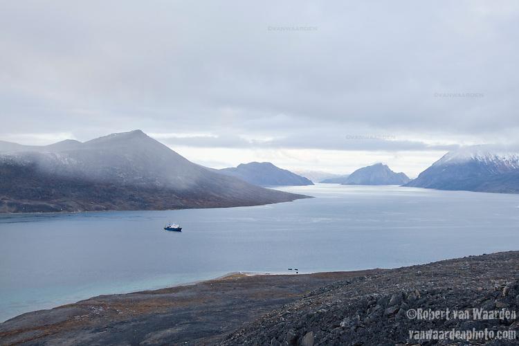 A ship lies at rest in the still waters around Qikiqtarjuaq, Baffin Island, Nunavut, Canada.