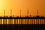 People walking over the huntington beach pier at sunset.