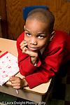 Parochial School Bronx New York  Kindergarten portrait of boy sitting at desk chin on hand vertical