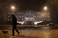 Pictured: A man with a dogks past the Greek Parliament in Syntagma Square, Athens, Greece. Monday 09 January 2017<br /> Re: Heavy snow fall and minus zero temperatures have affected most parts of eastern Europe and Greece.