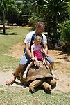 MUS, Mauritius, bei Rivière des Anguilles, La Vanille Crocodile Park & Nature Reserve: Vater und Tochter reiten auf einer Riesenschildkroete | MUS, Mauritius, near Rivière des Anguilles, La Vanille Crocodile Park & Nature Reserve: father and daughter riding a giant turtle