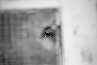 A boy looking through a hole in a broken window at the Varazdin refugee camp in the winter of 1992. <br /> <br /> In 1992 while volunteering at the Varazdin refugee camp Panos photographer Bjoern Steinz met and became close to Elvis, a Bosnian Muslim refugee, and his family. They shared the hardships of camp life together which Steinz documented. While the prints were archived for many years two of the images always returned to Bjoern's thoughts. 25 years later he set out to try and find out what had happened to Elvis and his family in the intervening years. Modern social media made the task surprisingly easy and they were reunited in Hadzici where Elvis now lives with his family.
