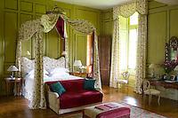 Sunlight streams in through the long elegant windows of this stunning bedroom