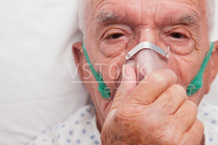 USA, Illinois, Metamora, Portrait of senior man with oxygen mask lying in hospital bed