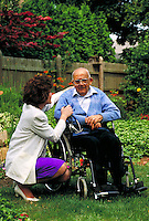 Home health care nurse visits with an elderly male patient in his garden.