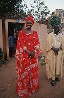 Mali. Bamako. The musician Oumou Sangare dressed in a red boubou laughs outside her home. © 1997 Didier Ruef
