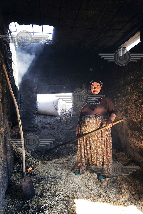 A woman feeds straw into a stone oven to keep a constant temperature while baking bread.