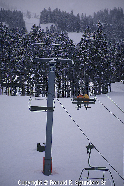 TWO SKIERS RIDE SKI LIFT AT BRECKENRIDGE COLORADO