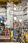 July 6, 2016. Greenville, South Carolina. <br />  Workers install the combustion cans on a 7HA.02 model GE gas turbine. The wire coils are to be connected to over  2600 sensors at the testing stand, where the turbine will be validated before being packaged an shipped to the client.<br />  At the General Electric Gas Turbine factory, engineers  design, produce, test and repair gas turbines for generating electricity. These turbines weigh more than 900,000 pounds and can create internal combustion temperatures up to 2,900 degrees F. Depending on the model, one of the GE turbines can produce enough electricity for half a million American households.