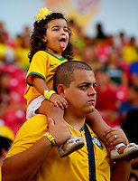 A young Brazilian fan sticks her tongue out as she watches sat on her father's shoulders