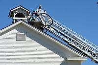 Curtis Morris (left), exhibits manager for the Shiloh Museum of Ozark History, reaches Tuesday, Oct. 13, 2020, to replace the mechanism that is used to ring the bell in the bell tower of the historic Shiloh Meeting Hall as Ron Skelton, an assistant chief for the Springdale Fire Department, operates a ladder truck to raise Morris into position at the building in Springdale. The original pre-Civil War-era bell is being curated in the museum's collection and a replacement has been fitted to the bell tower, but the mechanism to ring it needed to be improved. Visit nwaonline.com/201014Daily/ for today's photo gallery.
