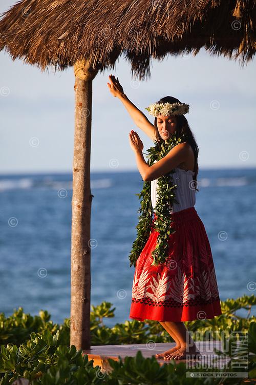 Young Hawaiian woman practicing hula in a beachfront gazebo at sunset