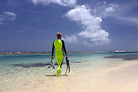Woman (MR) in a wetsuit with snorkeling equipment walking in the water along a beach in Cayman Brac, Cayman Island