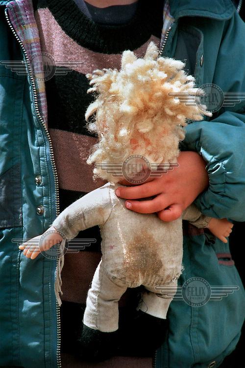 A young refugee carrying a doll crosses the border at Blace, having fled the war in Kosovo.