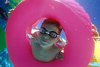 Kid peering through pool floats.