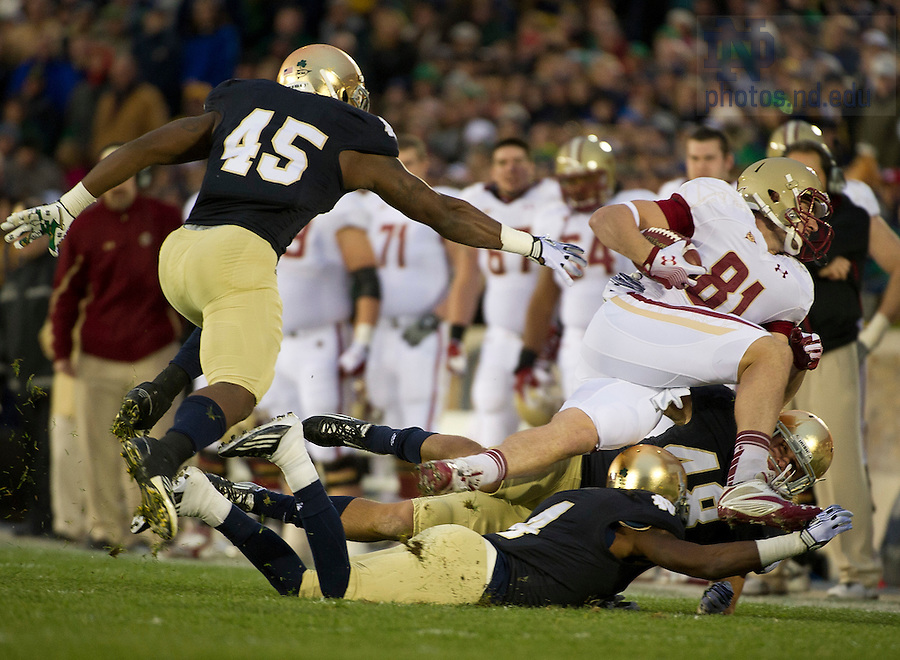 November 19, 2011; Notre Dame Fighting Irish cornerback Gary Gray (4) and inside linebacker Dan Fox bring down Boston College Eagles tight end Chris Pantle (81) during the first quarter against the Boston College Eagles. Photo by Barbara Johnston/University of Notre Dame.