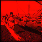 Fishermen in Padang Bai in Bali carry their outrigger canoe to dry ground after a day of fishing.