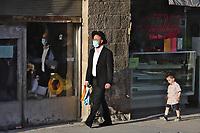 Un haredi vistiendo un barbijo junto a su hijo caminan por la  vacía calle principal del barrio ultraortodoxo, Mea Shearim en Jerusalén. <br /> En un esfuerzo por detener el contagio del COVID 19 el gobierno israelí decreto el uso obligatorio de barbijos en las calles. La pandemia ha afectado fuertemente a la comunidad Haredi. El gobierno israelí decreto un confinamiento limitando la salida a 100 metros de los hogares. <br /> Foto Quique Kierszenbaum