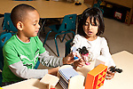 Education preschool 3-4 year olds boy and girl playing together with small dolls and furniture talking