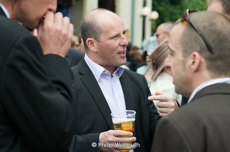 Businessmen drinking beer outside a pub in Ascot.