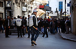A policeman carries a baseball bat during a tense afternoon in downtown Tunis, Tunisia, Jan. 16, 2011. Snipers were later reported in the area near the Interior Minstry. Rumors flew, some saying members of the former regime were firing, others blaming it on foreigners who had come to cause trouble.