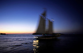 Florida, USA. Blurred silhouette of sailing ship against pink sky at dusk in Key West.