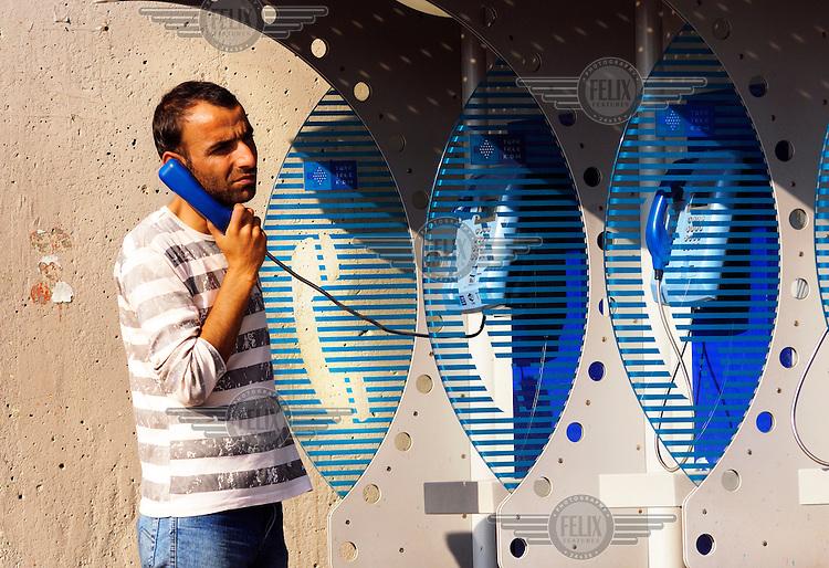 A man using a public telephone.