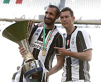 Calcio, Serie A: Juventus vs Crotone. Torino, Juventus Stadium, 21 maggio 2017.<br /> Juventus' Giorgio Chiellini, left, and Stephan Lichsteiner hold the trophy during the celebrations for the victory of the sixth consecutive Scudetto at the end of the Italian Serie A football match between Juventus and Crotone at Turin's Juventus Stadium, 21 May 2017. Juventus defeated Crotone 3-0.<br /> UPDATE IMAGES PRESS/Isabella Bonotto