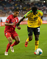 NASHVILLE, TN - JULY 3: Kemar Lawrence #20 tries to hold off Reggie Cannon #14 during a game between Jamaica and USMNT at Nissan Stadium on July 3, 2019 in Nashville, Tennessee.