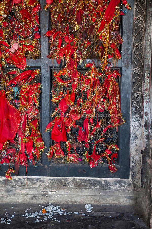 India, Dehradun.  Visitors tie bits of red cloth to the window latticework as a symbol of prayers offered at the Sikh Temple Durbar Shri Guru Ram Rai Ji Maharaj, built in 1707.  Rice on the step.
