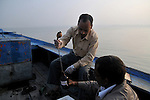 Gopal Pandey (38) collecting water from Ganga at Varanasi for checking the pollution level in it at the laboratory of Sankat Mochan Foundation. He is working as a lab assistant at Sankat MochanFoundation for last 18 years, Sankat Mochan Foundation is an NGO headedby Prof. Vir Vadra Mishra and it works towards making the Ganga water-pollution free in Varanasi. Uttar Pradesh, India.