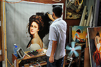 An artist at work in the street. Dafen is home to an art industry producing replicas, as well as original works, of pieces by the world's great artists for sale overseas. The success of this business has attracted more and more trained artists to the town seeking an opportunity to make a living.