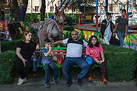 Armenia. Yerevan.  A statue of a Ceratosaurus, a prehistorical animal, stands behind an Armenian family seated on a bench in the amusement park located in the city center. Ceratosaurus was a carnivorous theropod dinosaur in the Late Jurassic period. Yerevan, sometimes spelled Erevan, is the capital and largest city of Armenia. 1.10.2019 © 2019 Didier Ruef