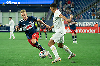 FOXBOROUGH, MA - MAY 1: Miles Robinson #12 of Atlanta United FC passes the ball under pressure from Adam Buksa #9 of New England Revolution during a game between Atlanta United FC and New England Revolution at Gillette Stadium on May 1, 2021 in Foxborough, Massachusetts.