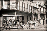 Horse carriages carry tourists on relaxing tours of the French Quarter  in New Orleans, Louisiana.  The Spanish-style architecture of the French Quarter dates back hundreds of years to the 1700s.  It is distinctive for the intricate, wrought iron balconies, central courtyards, and quaint doors and windows.